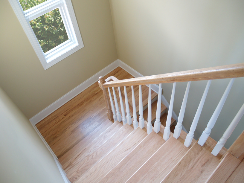 View down a Hamilton wooden stairwell installation with a window.